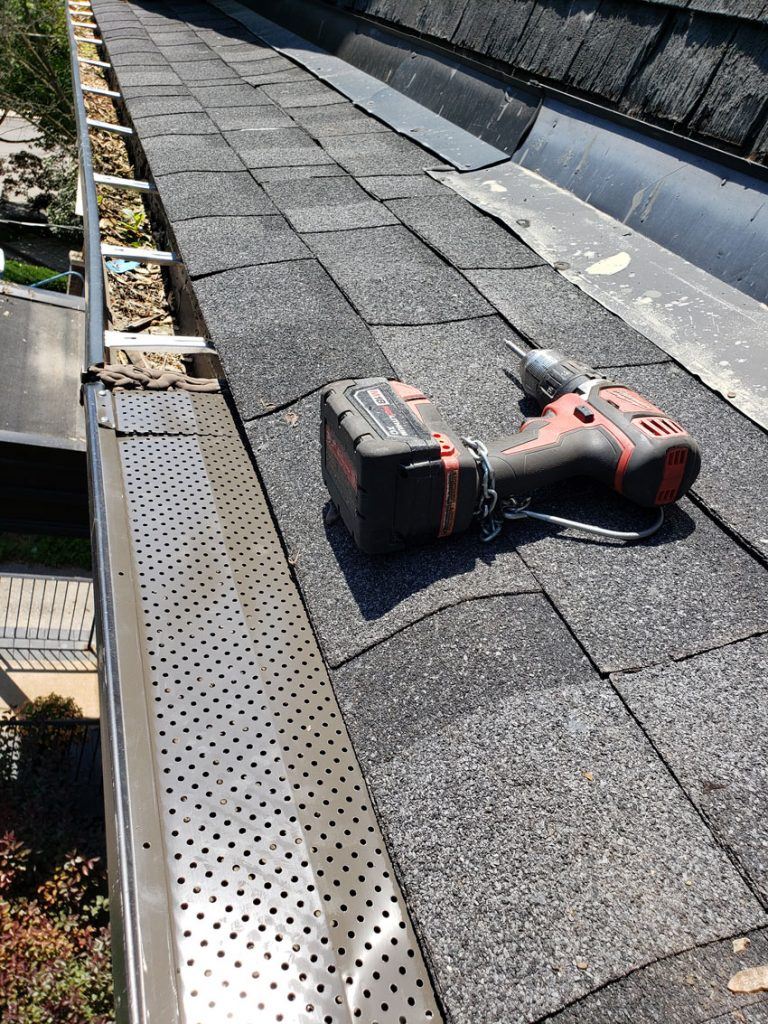 installing gutter guard to protect eavestrough from dirby build up